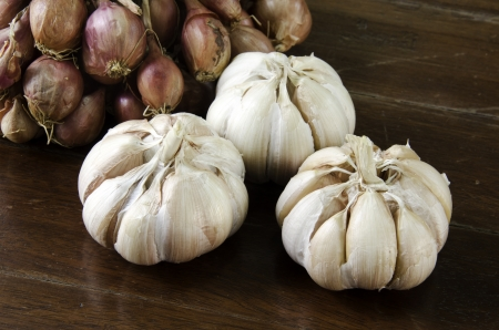 Garlic and red onions with a wooden floor backdrop.