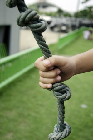 Childs hand holding a rope in the grass. photo