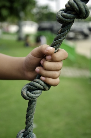 Childs hand holding a rope in the grass.