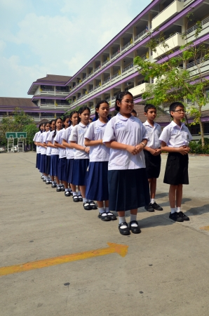 Students stand in line with the school building as a backdrop