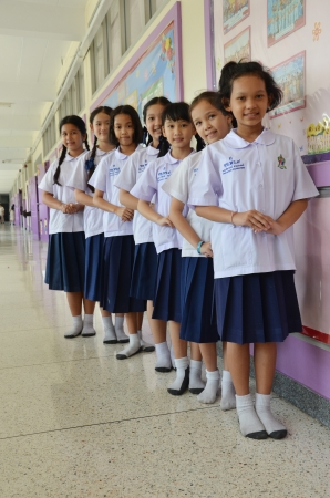 Students stand in line with the school building as a backdrop  Stock Photo - 22625880