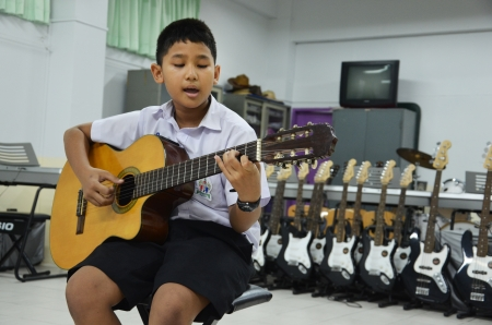 Child in a classroom playing guitar music  Editorial