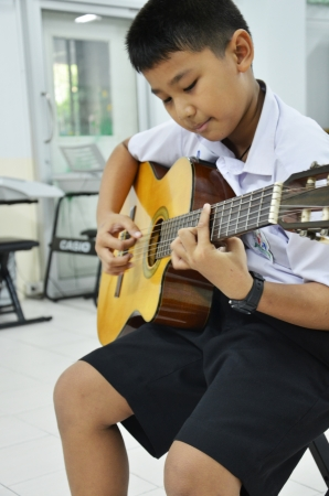 Child in a classroom playing guitar music