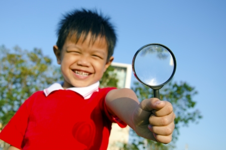 Boy with magnifying glass in the sky as a backdrop