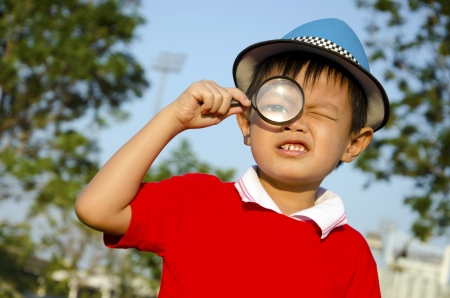 Boy with magnifying glass in the sky as a backdrop   photo