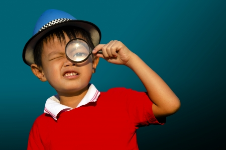 Child with a magnifying glass with a dark background  photo