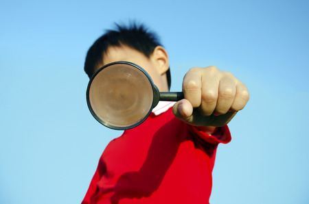 Kids with magnifying glass with sky as a backdrop  photo