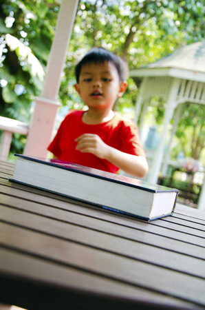 Book on a table with pictures of children in the background   photo