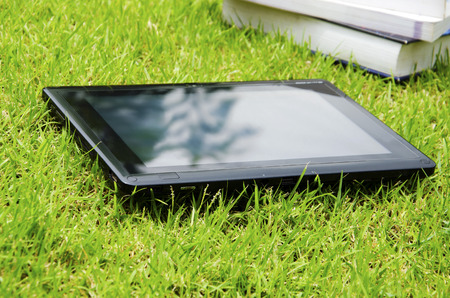 The tablet has a background as a lawn.
