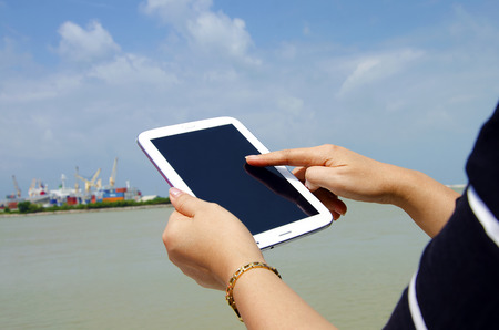 Tablet with sea and sky in the background.