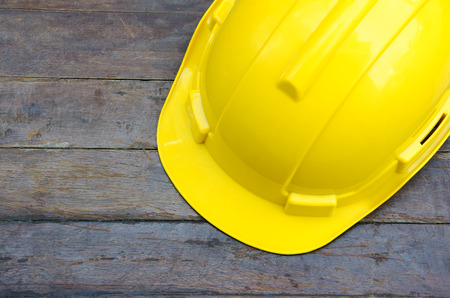 obrero trabajando: ingenieros sombrero con un suelo de madera en el fondo. Foto de archivo