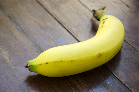 bannana: Bananas on a wooden floor in the background. Stock Photo