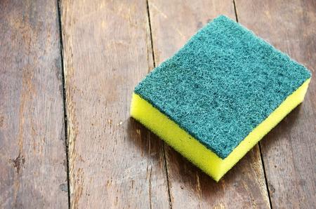 lavar platos: Lavar platos esponja con un suelo de madera en el fondo.