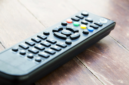 ok button: OK button on the TV remote control with a wooden floor in the background.