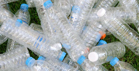 Pile from plastic bottles with a lawn in the background.