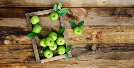Organic green apples on the wooden floor.