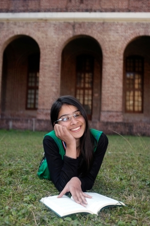 Cheerful Indian girl lying over grass and studying in campus lawn  photo
