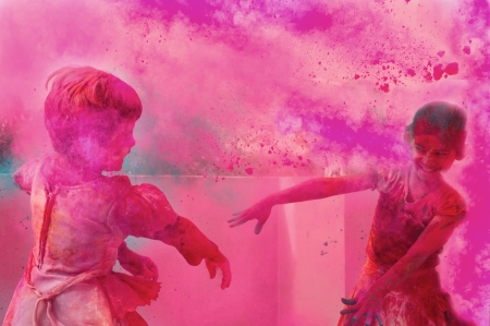 customs and celebrations: Two little kids playing with colors   gulal on holi, an Indian festival  Stock Photo