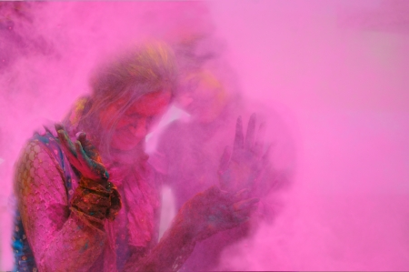 customs and celebrations: Two females standing in the fog of colors  gulal during Holi celebration in India