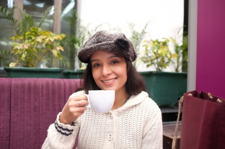 Cute smiling woman drinking a coffee sitting inside in cafe restaurant  photo