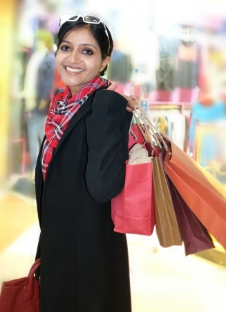 Beautiful Indian shopping woman, happy holding colorful shopping bags in hand. photo