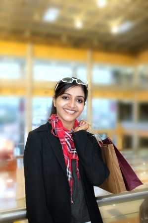 Pretty Indian woman smiling with lots of shopping bags. photo