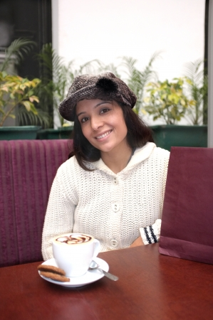 Young attractive woman sitting in a cafe with coffee on table. photo