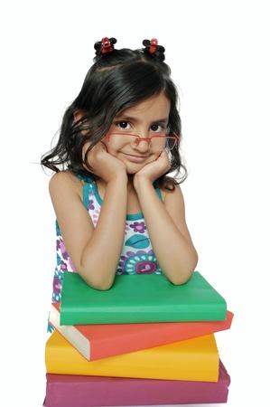 fille indienne: Enfants  éducation: Petite fille mignonne indienne assis avec une pile de livres, sur fond blanc isolé.