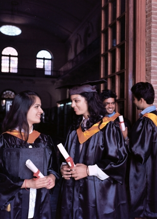 Group of happy Indian students in their graduation dress, smiling with their degree. photo