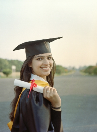 masters degree: Indian College graduate holding diploma and smiling after graduation ceremony.