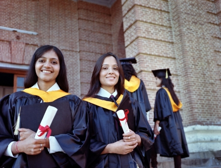 masters degree: Two Pretty Indian College graduates happy after getting degree in the campus. Stock Photo