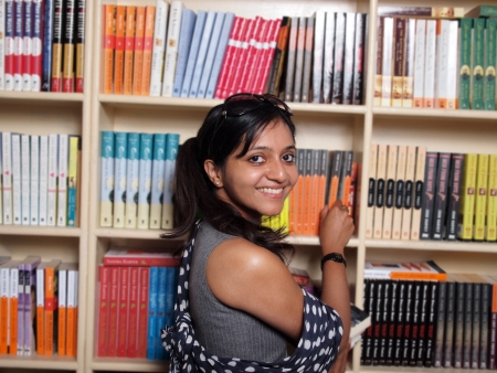 education choice: Indian college student selecting books in the campus library. Stock Photo