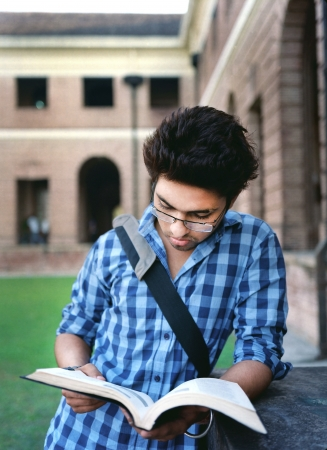 Young Male College student reading his notes before examination outside the campus. photo