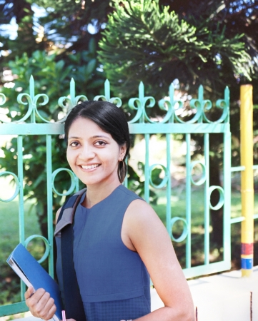 Young College student holding books, happy going to campus. photo