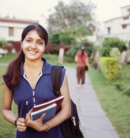 graduacion de universidad: Estudiante feliz Colegio indio caminando en el campus, con los libros en la mano.