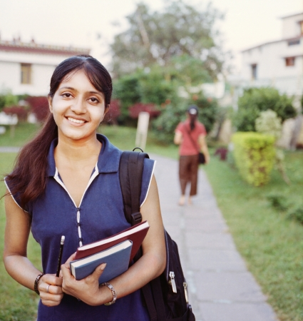 Happy Indian College student walking in the campus, with books in hand. photo