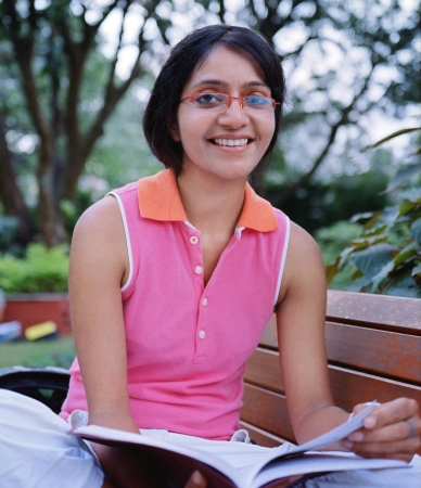 mixed race ethnicity: Cute Indian College student  sitting on a bench and reading a book. Stock Photo