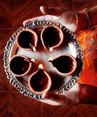 red oil lamp: Human hands holding plate of oil lamps on Deepawali in India.