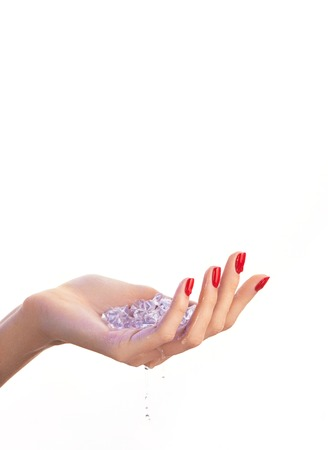 caucasian water drops: Female hand with red nail polish, blue ice cubes inside it and drops of water, isolated on white background