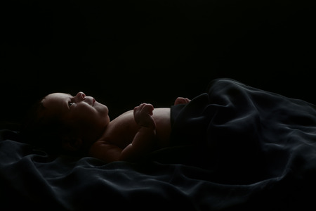 0 3 months: Cute newborn baby shot in studio lying, covered with soft black blanket, isolated on black background Stock Photo