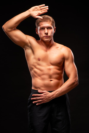 Muscular shirtless sportsman looking at camera with raised hand, demonstrating biceps, triceps, pectoral and abdominal muscles, dressed in black shorts, isolated on black background