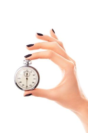 Female hand holding stopwatch set to thirty seconds, with nails covered with black nail polish