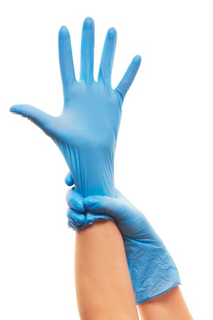 sterilized: Close up of female doctors hands putting on blue sterilized surgical gloves against white background