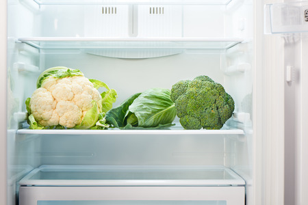 Cauliflower, green cabbage and green broccoli on shelf of open empty refrigerator. Weight loss diet concept.