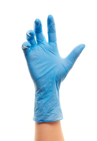 medical gloves: Close up of female doctors hand in blue sterilized surgical glove against white background
