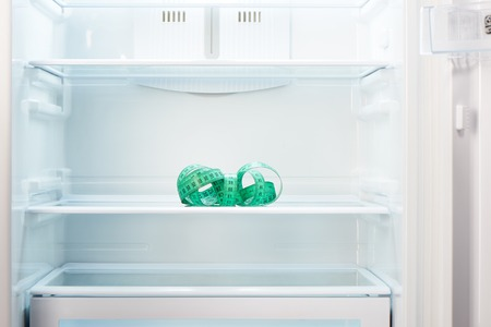 refrigerator with food: Green measuring tape on shelf of open empty refrigerator. Weight loss diet concept.