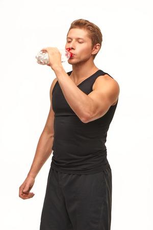 sediento: Sediento muscular guapo deportista potable joven despu�s del entrenamiento duro, aislado en fondo blanco