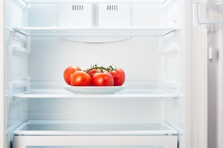 Branch of red tomatoes on white plate in open empty refrigerator. Weight loss diet concept.