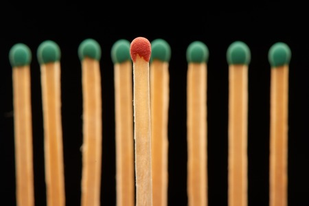 household accident: Red wooden match standing in front of defocused set of eight green matches, isolated on black background