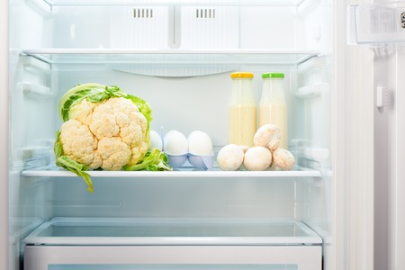 Cauliflower, white eggs, champignon mushrooms and two glass bottles of yoghurt on shelf of open empty refrigerator. Weight loss diet concept. Stock Photo
